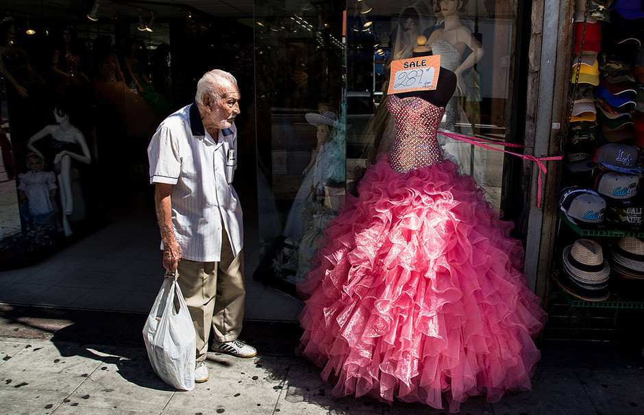 street photo of old man standing next to bright pink dress