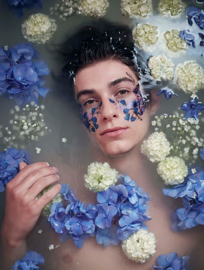 portrait of young man in water covered in white and blue flowers