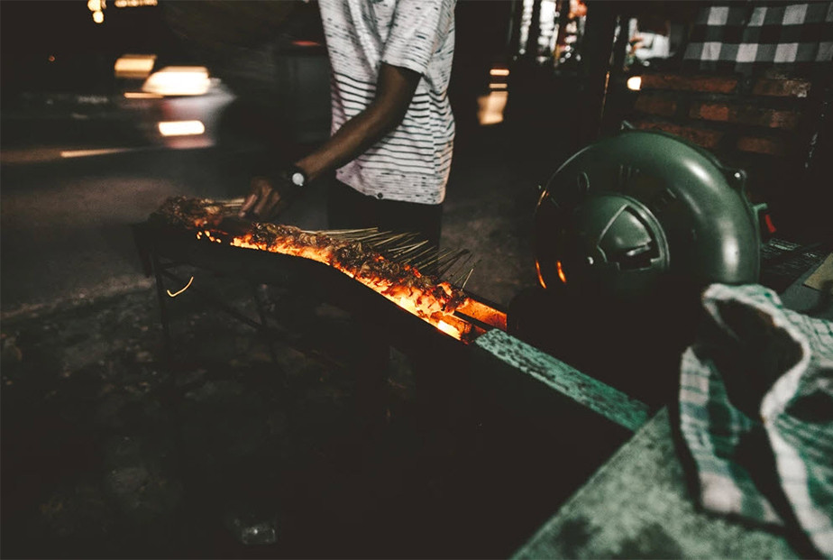 travel photography street vendor cooking food on coals