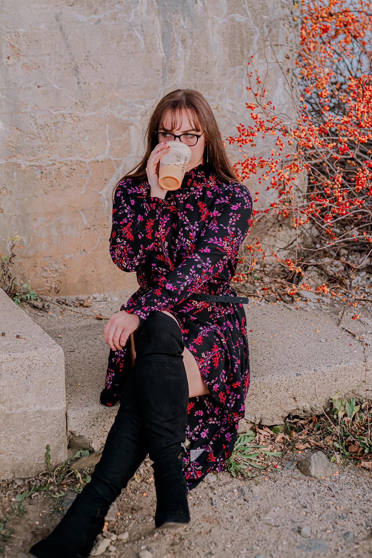 woman holding a book, next to a coffee mug