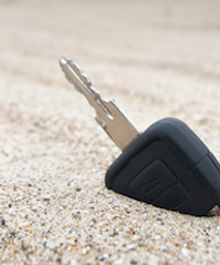 new car key sticking out of sand