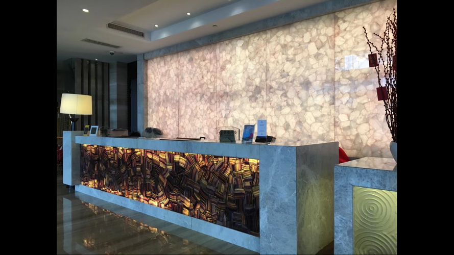 Backlit reception desk and wall decoration in luxurious Amethyst and White Quartz