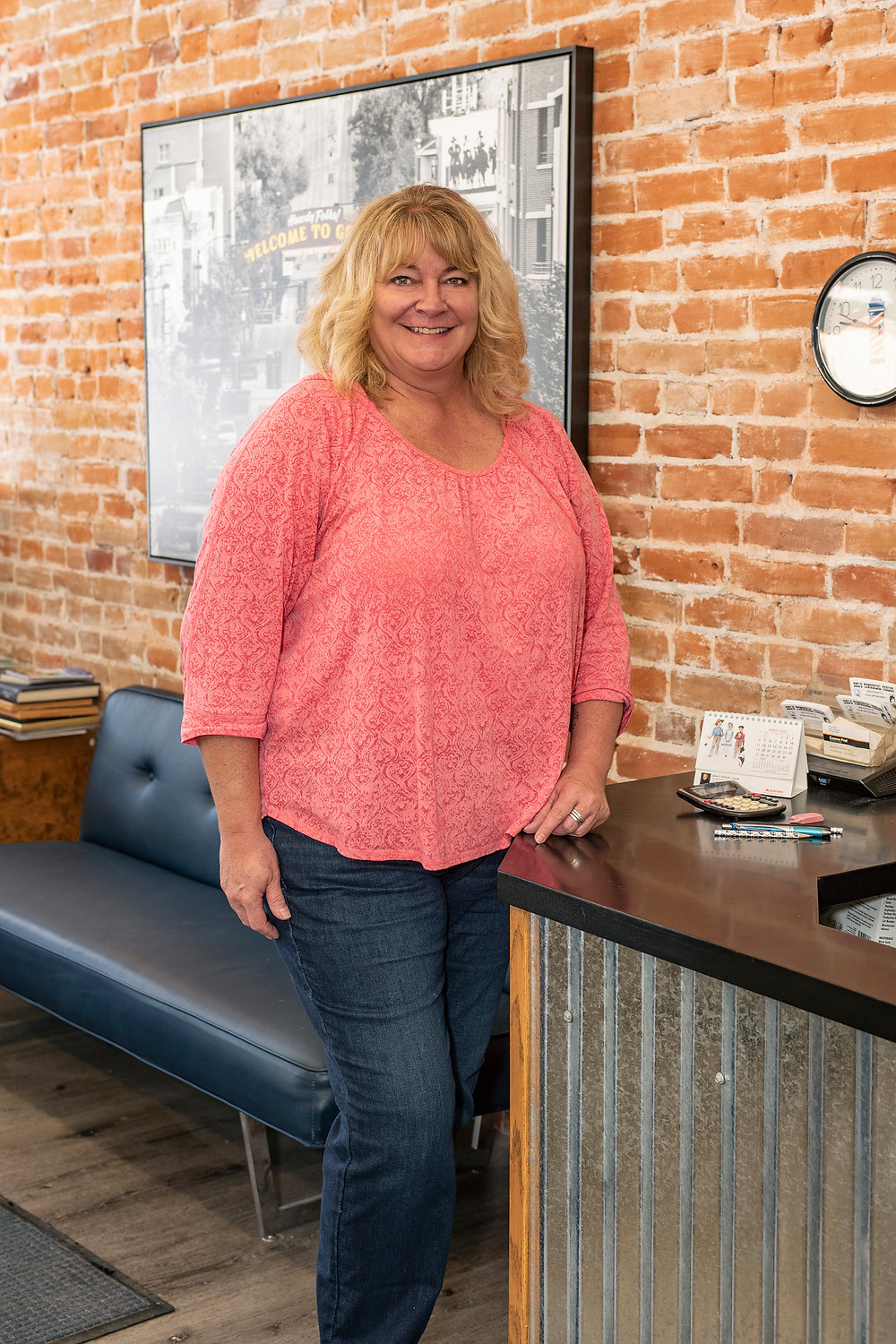 Barb Robie wearing a pink shirt standing in her salon.
