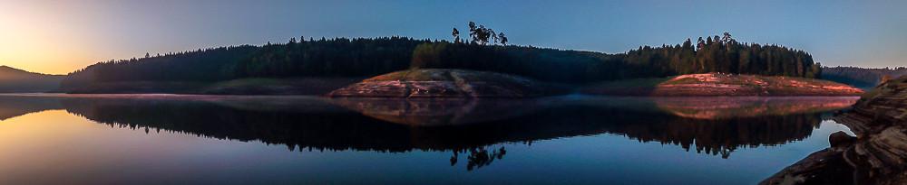 effet miroir sur un lac au lever du jour sous ciel clair
