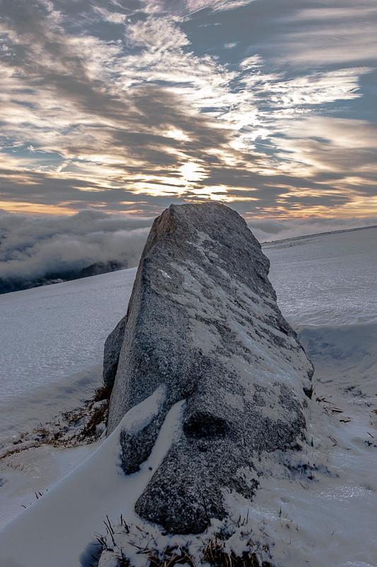 rocher solitaire sur une colline enneigée en fin de journée