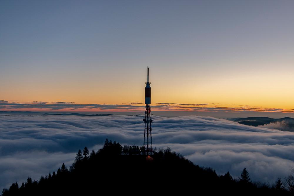 antenne relais au dessus du brouillard au coucher du soleil