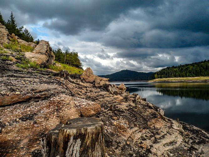 berge et rive asséché d'un lac sous ciel d'orage