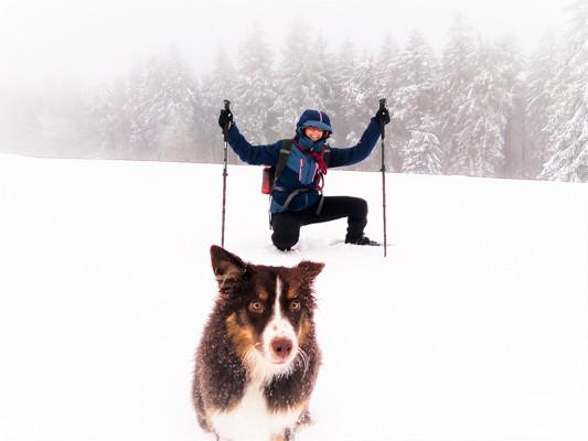 Une randonneuse pose avec son chien dans un paysage enneigé