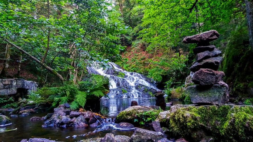 la cascade Charlemagne entourée de végétation au milieu de la forêt