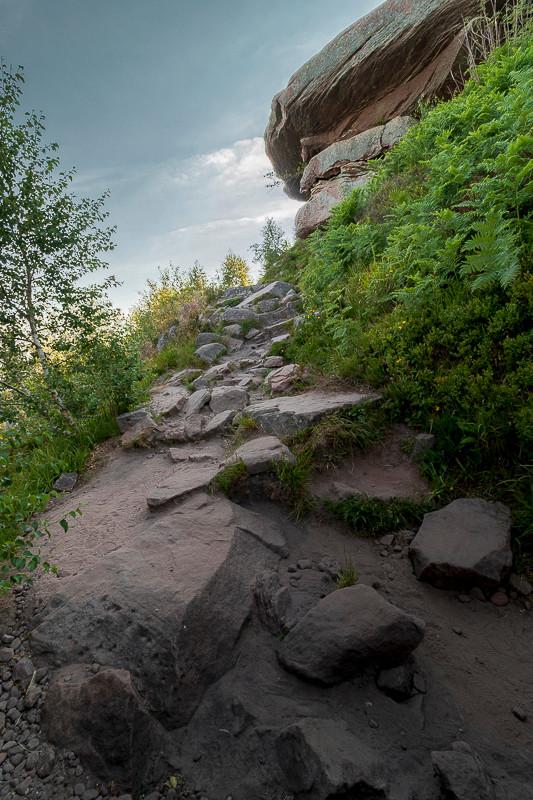 sentier rocailleux vers un sommet entouré de verdure