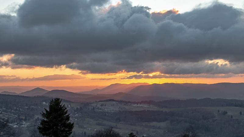 Ciel nuageux et rayons de soleil au dessus de vallées en fin de journée
