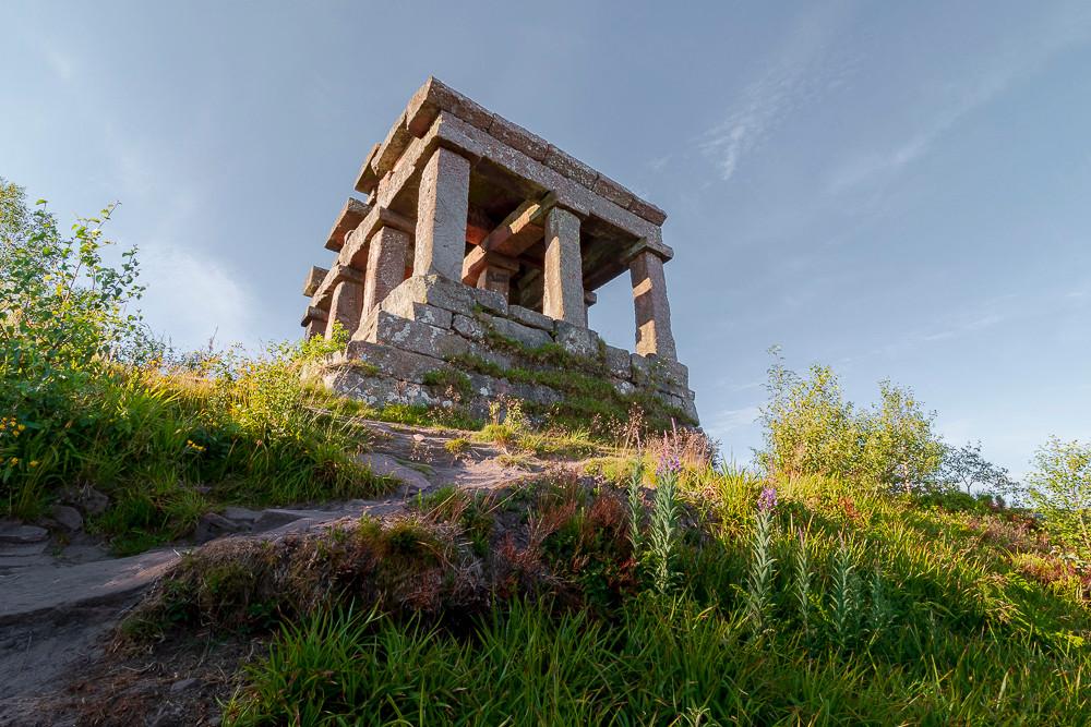 temple d'architecture Gallo-Romaine entouré de verdure et de végétation sous un ciel voilé