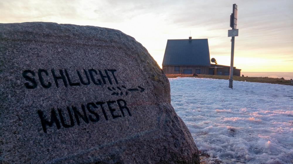 signalisation gravée dans une roche et refuge en arrière plan
