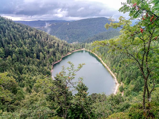 vue d'un petit lac de montagne entouré de forêt sous un ciel nuageux