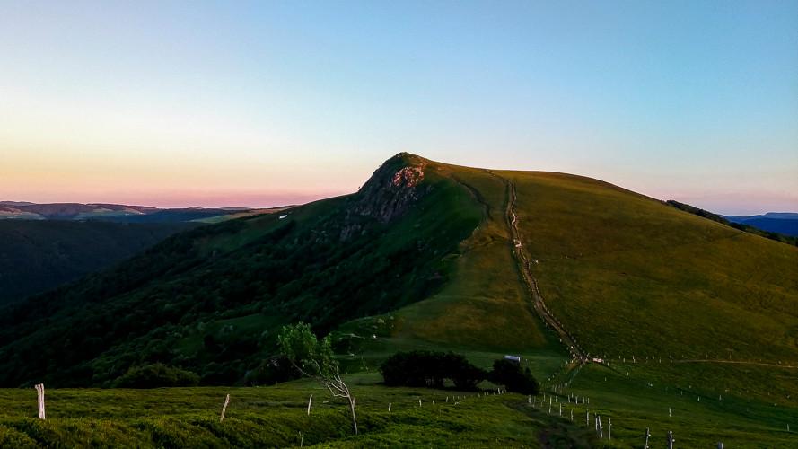 sommet semi-montagneux entouré de prairies et paturages au crépuscule