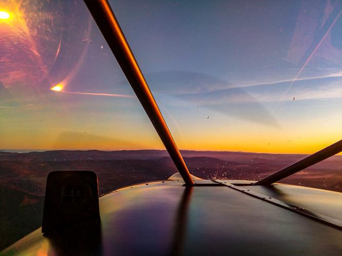 vue aérienne depuis l'intérieur d'un cockpit d'ULM au soleil couchant
