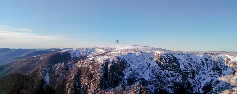 un hélicoptère survole montagnes enneigées et falaises