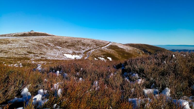 prairies montagneuses et un refuge au sommmet d'une colline