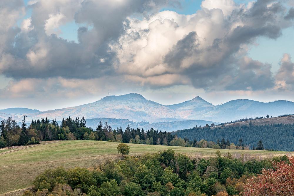 collines et pâturages devant montagnes sous ciel nuageux