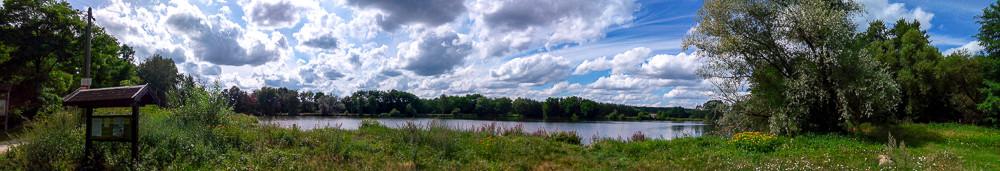 panorama d'un étang et la forêt autour sous ciel de cumulus