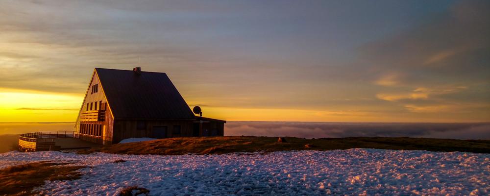 un refuge au sommet d'une montagne au soleil couchant