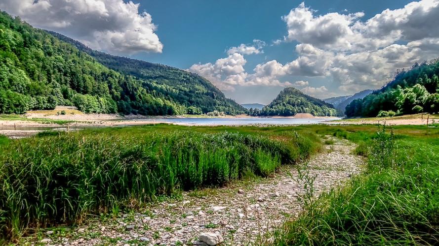 lac entouré de montagnes boisées au lit asséché ou poussent les hautes herbes