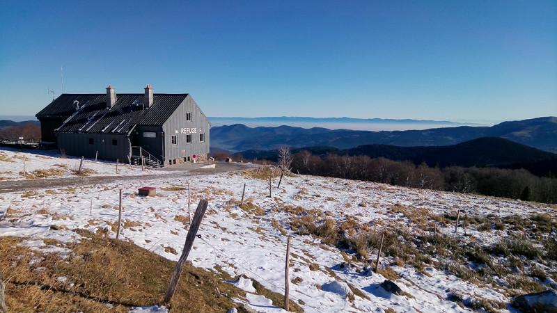 Un refuge en milieu semi-montagneux sous un ciel bleu dégagé