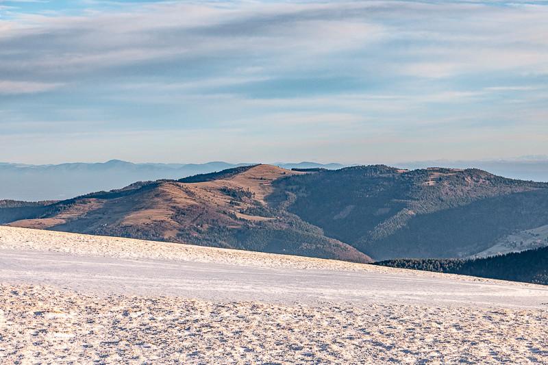 montagnes et forêts depuis une colline enneigée