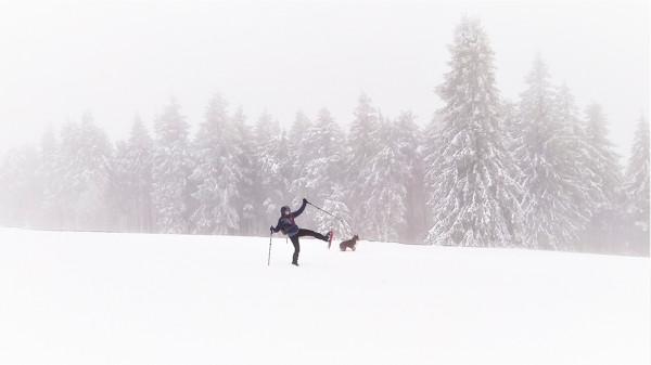 une randonneuse et son chien dans un paysage enneigé et brumeux