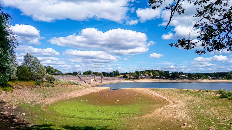 réservoir asséché et son barrage sous les cumulus et le ciel bleu
