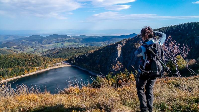 photographe randonneuse face à un paysage de forêt, collines et lac