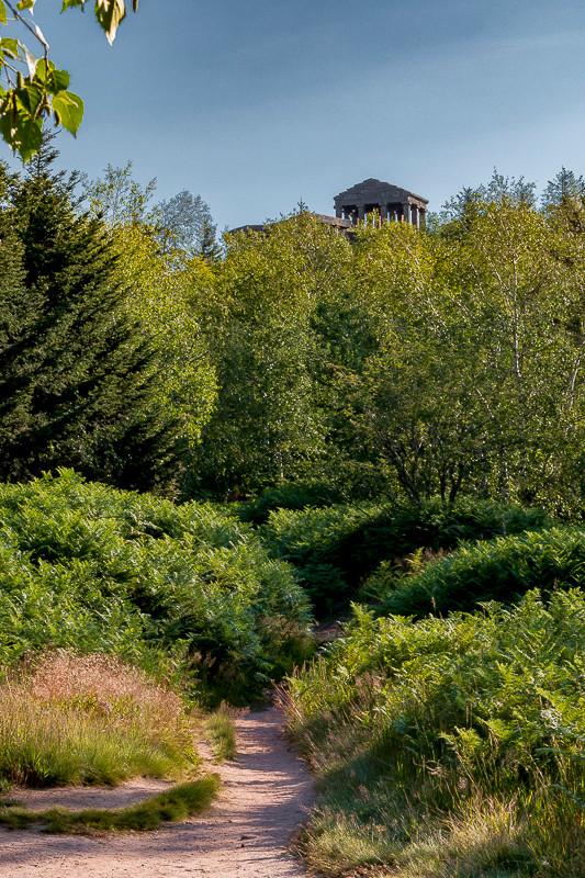 sentier pédestre qui s'enfonce dans la végétation avec un temple gallo-romain au sommet