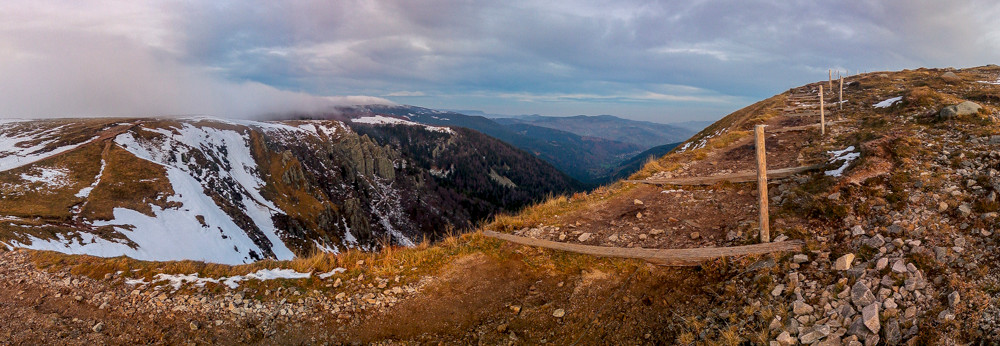 sentier de randonnée qui surplombe les falaises sous un ciel voilé