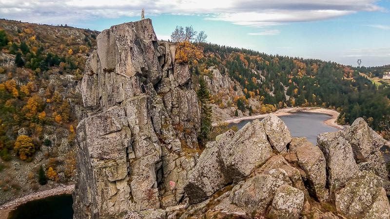 paysage de promontoir rocheux surmonté par statue de la vierge vue sur le lac et forêt