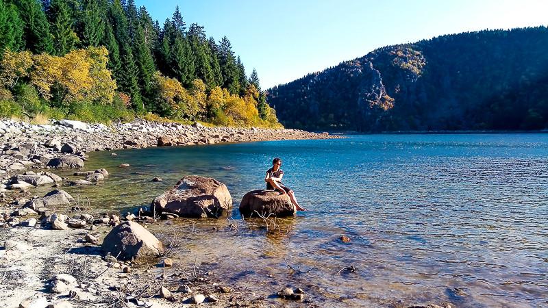 femme assise sur un rocher sur le lac entouré de falaises et de forêt