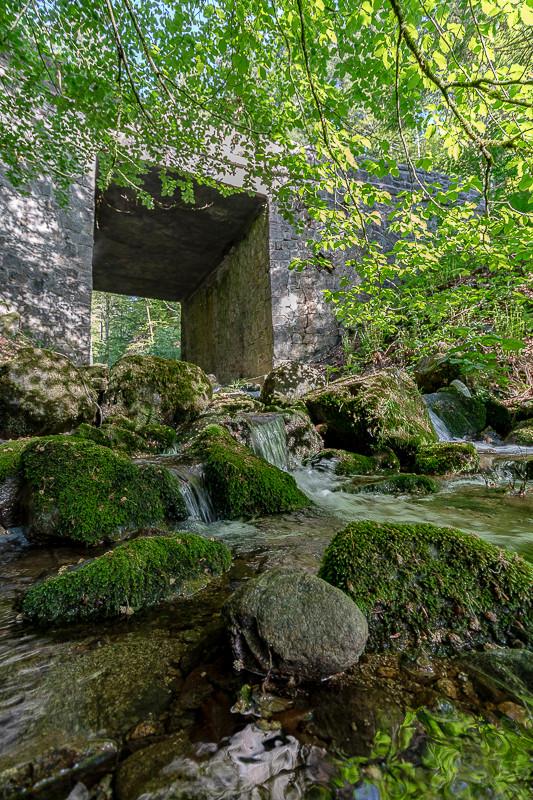 rivière qui passe dans les roches, sous un pont de pierres