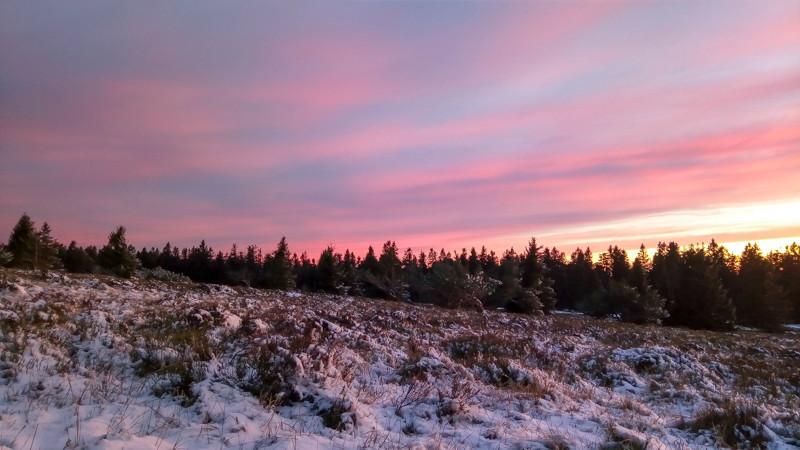 pente d'une prairie à moitié couverte de neige au coucher du soleil