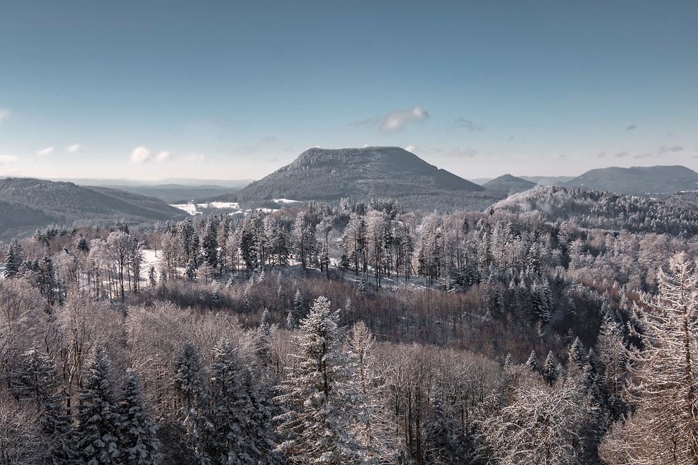 montagne boisée du Climont sous un ciel bleu pastel