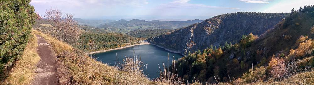 panorama depuis les hauteurs sur un sentier lac en contrebas entouré par falaises et forêts