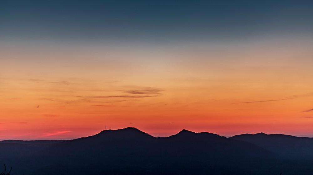 formes de montagnes en ombre chinoise sous horizon rougoyant