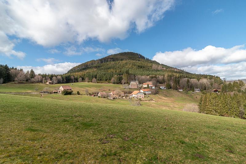 petit hameau au pied d'une montagne boisée
