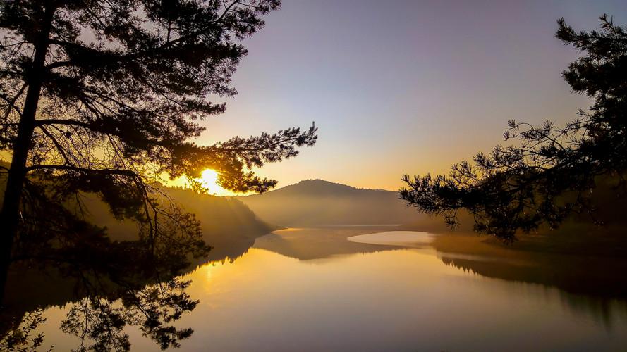 aube et ciel clair sur un lac avec arbres et collines en ombres chinoises