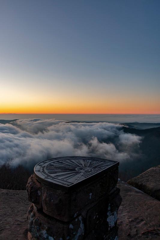table d'orientation face au soleil couchant et brume dans la vallée