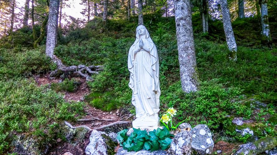 sculpture de la Vierge entouré de vagatation buissons et arbres