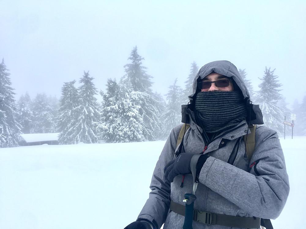 un randonneur de face dans un environnement hivernal brumeux