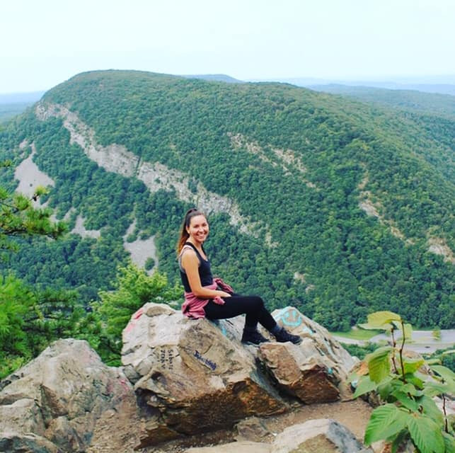 Addiction Therapist Brooke Aymes sitting on top of Mt. Tammany in New Jersey