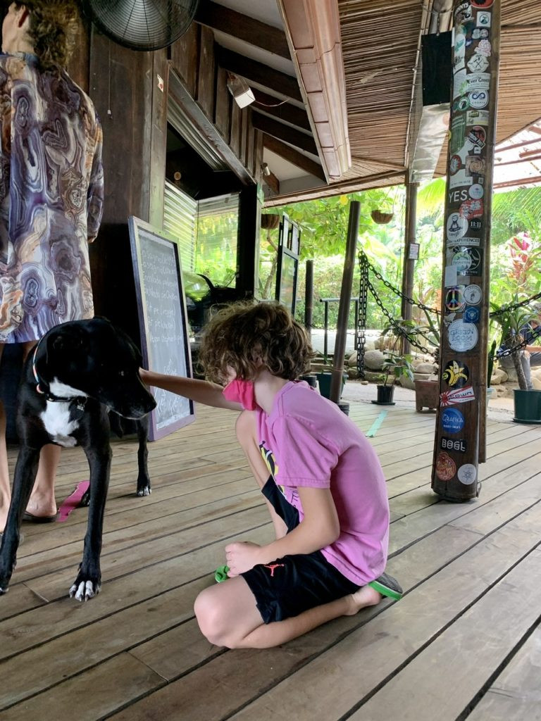 Boy and dog in rainforest cafe costa rica