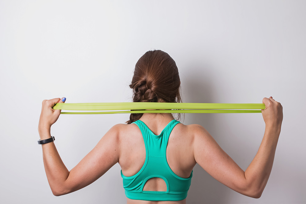 Woman stretching her shoulders with resistance band