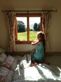 Girl looking through La Roulotte window