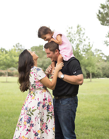 Pregnant mom in a flowing dress poses for camera wih husband and daughter up on his shoulders.